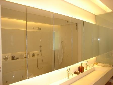 Espelho retro-iluminado sobre armário de marcenaria