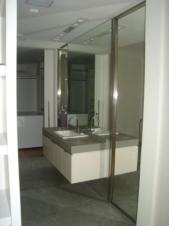 Espelho sobre bancada e porta de inox revestida